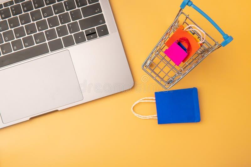 O saco de compras e o trole de papel coloridos vão para baixo de flutuar o fundo cor-de-rosa para o espaço da cópia imagens de stock royalty free