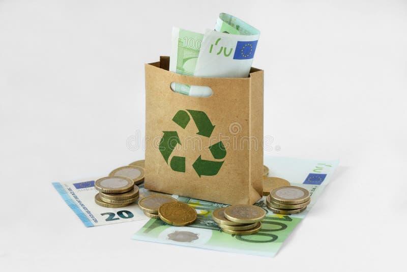 O saco de compras de papel com verde recicla o símbolo no dinheiro - ecologia fotografia de stock royalty free