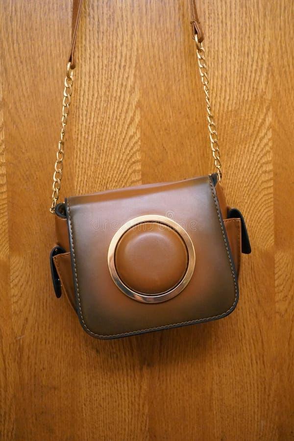 O saco de couro luxuoso bonito do marrom do ` s das mulheres pesa na porta de madeira imagens de stock royalty free