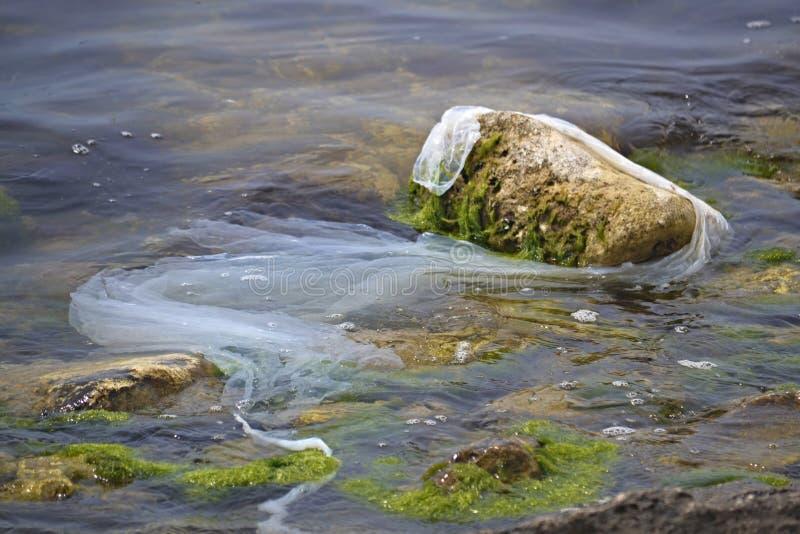 O saco de pl?stico, o lixo e as garrafas do polietileno jogam em terra o mar pl?stico N?o-recicl?vel eventualmente para quebrar a imagens de stock