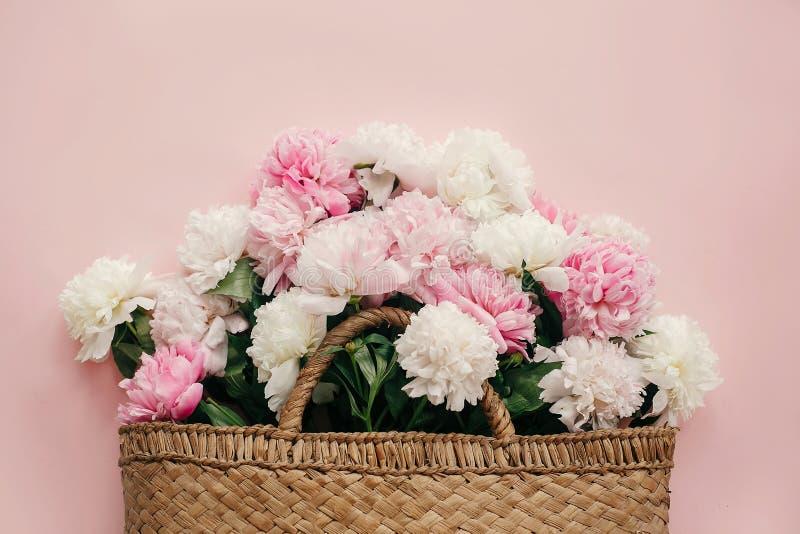 O saco rústico da palha à moda com as peônias brancas e cor-de-rosa no papel cor-de-rosa pastel, coloca horizontalmente com espaç fotografia de stock