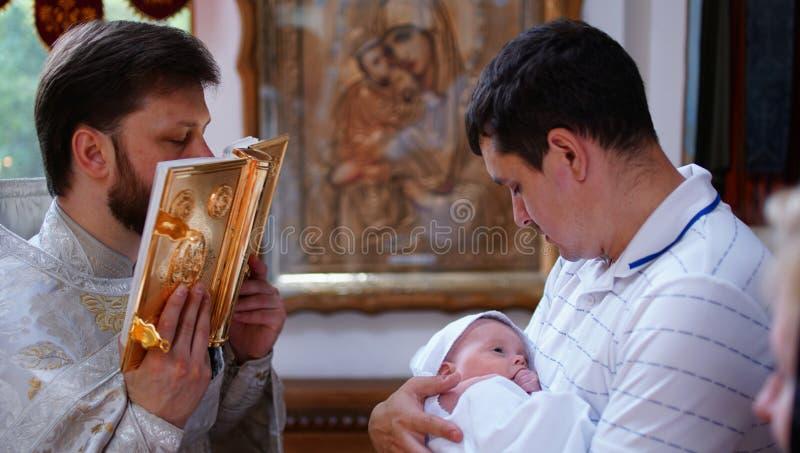 O sacramento do batismo Batizando o bebê Criança, padre e padrinho fotos de stock
