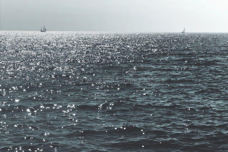 O sailng do veleiro no oceano iluminou-se pela luz solar no por do sol fotografia de stock