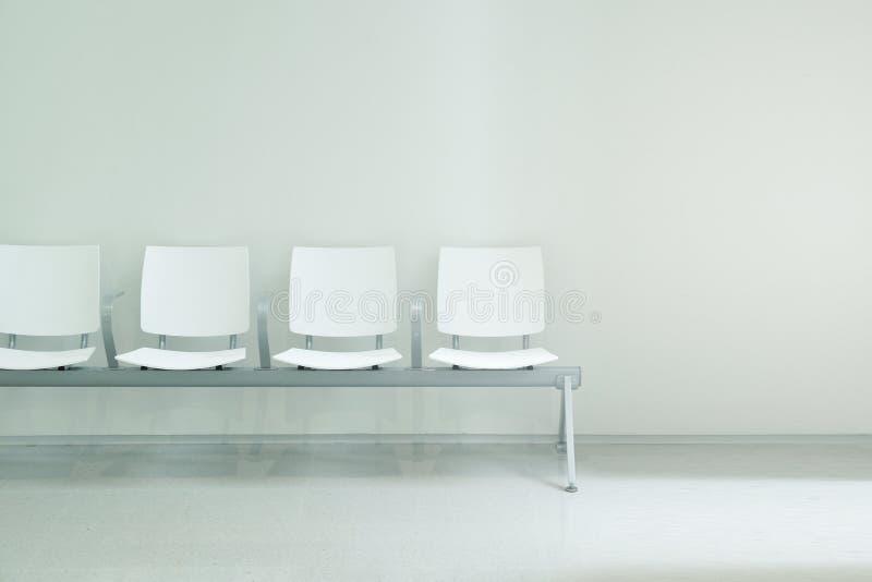 O salão de espera preside a formação de uma fileira contra um fundo branco da parede fotos de stock