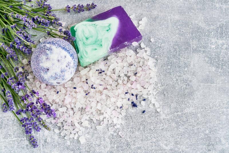 O sal da alfazema, o sabão e a bomba essenciais do banho com parte superior das flores vie foto de stock royalty free