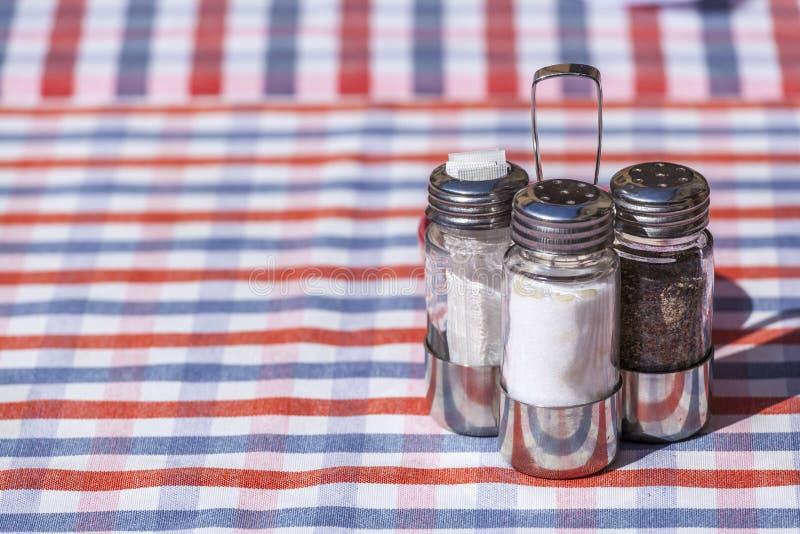 O sal, a pimenta e o palito ajustaram-se sobre uma tabela exterior do restaurante imagens de stock royalty free