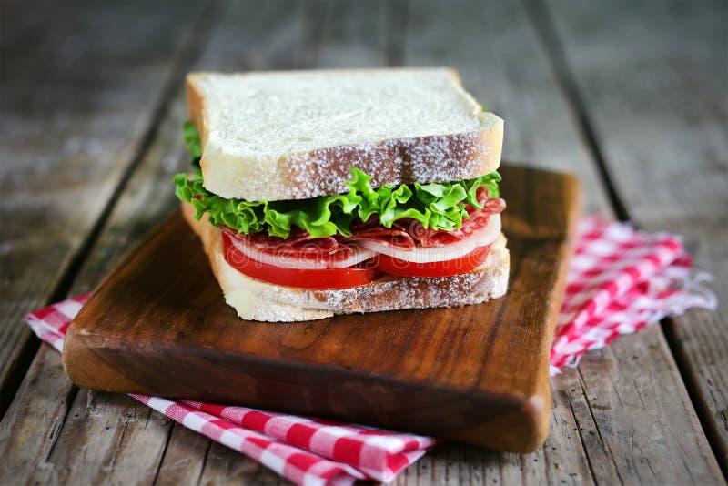 O salame e o queijo brindam o sanduíche com tomates e alface imagens de stock royalty free