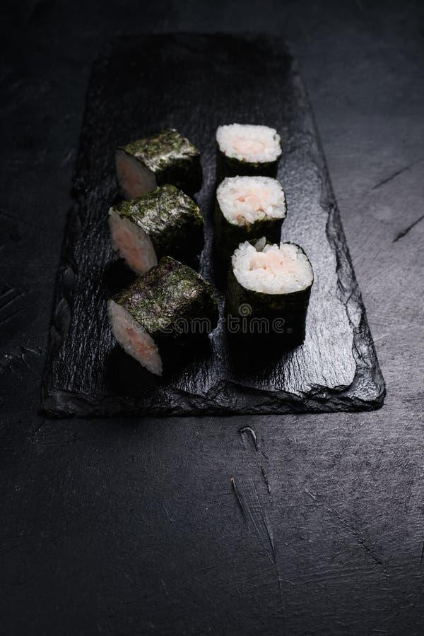 O salmão do sushi rola a culinária escura do asiático do fundo fotografia de stock