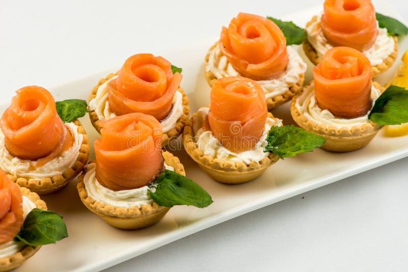 O salmão fumado salgado na cesta é feito sob a forma de uma rosa em uma placa branca imagem de stock