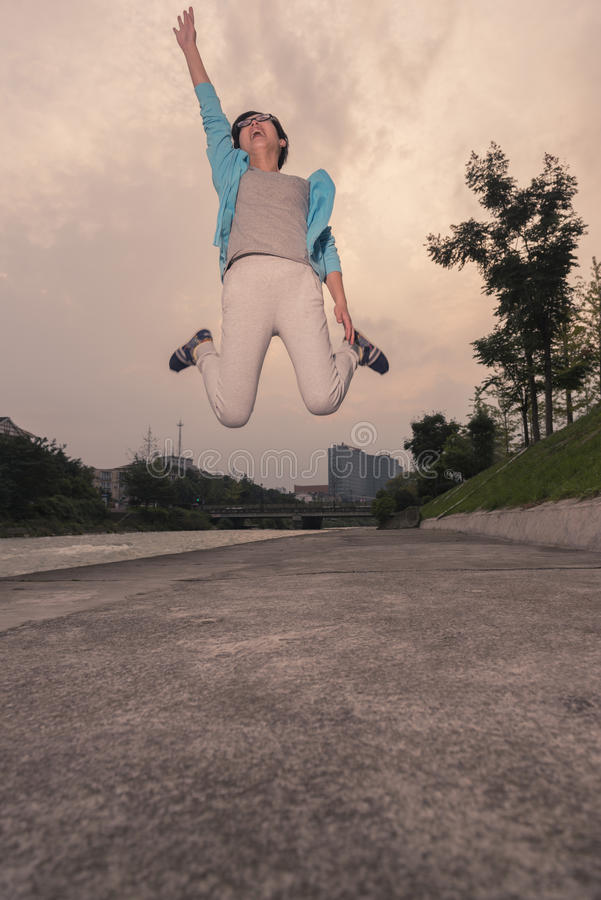 O salto da jovem mulher fotografia de stock royalty free