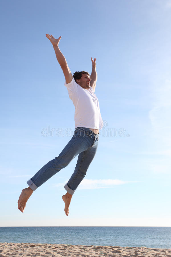 O salto do homem feliz na praia foto de stock royalty free