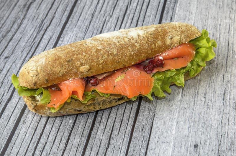 O sanduíche apetitoso encontra-se em um fundo de madeira sanduíche em um bolo longo com salada e salmões fotografia de stock