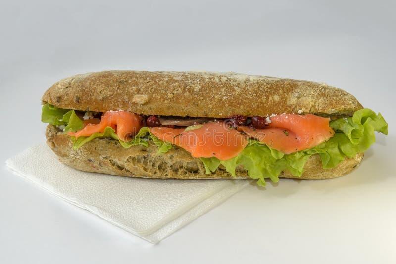 O sanduíche apetitoso está em um fundo branco sanduíche em um bolo longo com salada fotos de stock royalty free