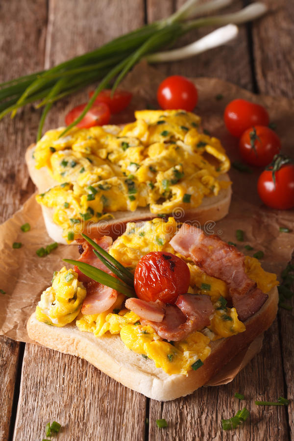 O sanduíche caseiro com ovos mexidos, o bacon e os tomates fecham-se imagem de stock royalty free