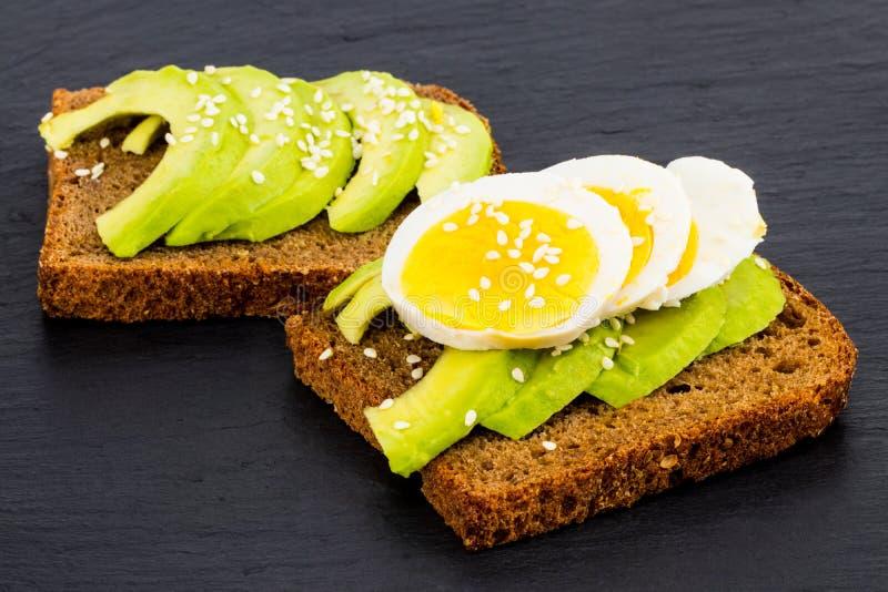 O sanduíche com abacates e ovos, em um fundo de pedra preto, cobre fotografia de stock royalty free