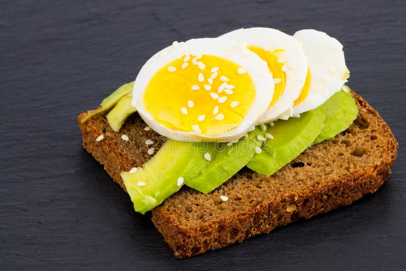 O sanduíche com abacates e ovos, em um fundo de pedra preto, cobre imagens de stock royalty free