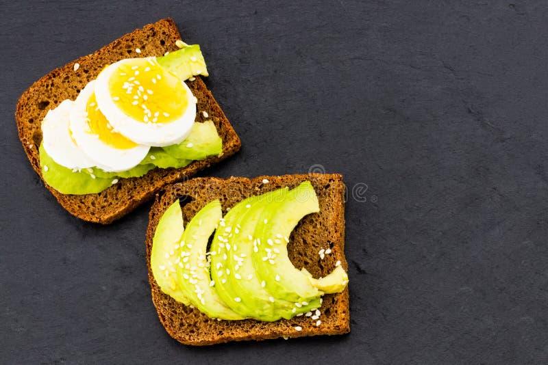 O sanduíche com abacates e ovos, em um fundo de pedra preto, cobre foto de stock