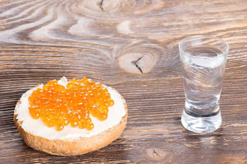 O sanduíche com manteiga e o caviar vermelho enfileiram com um vidro da vodca em um de madeira foto de stock