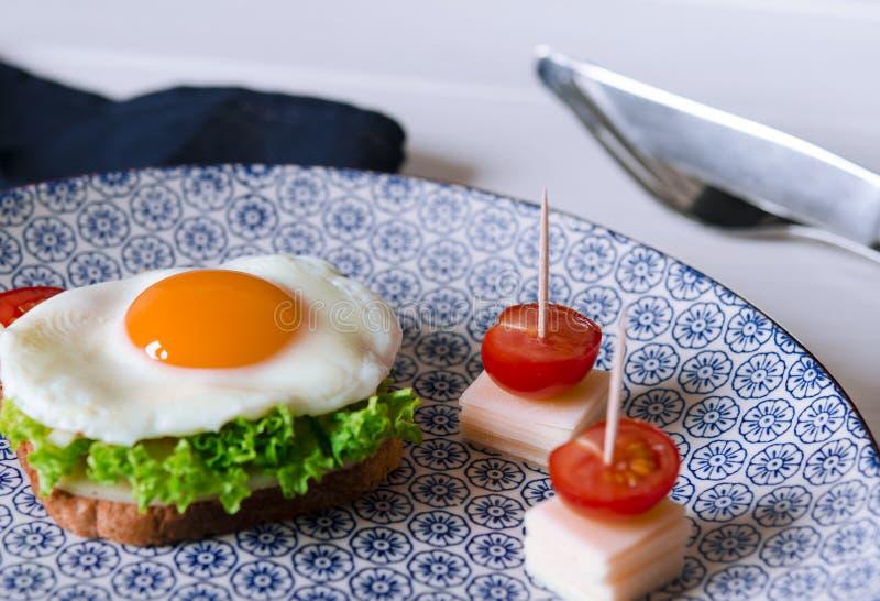 O sanduíche com ovo, presunto, queijo, brinde e salada deixa mentiras em uma placa com o tomate e o aneto fotos de stock