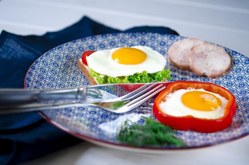 O sanduíche com ovo, presunto, queijo, brinde e salada deixa mentiras em uma placa com o tomate e o aneto imagem de stock