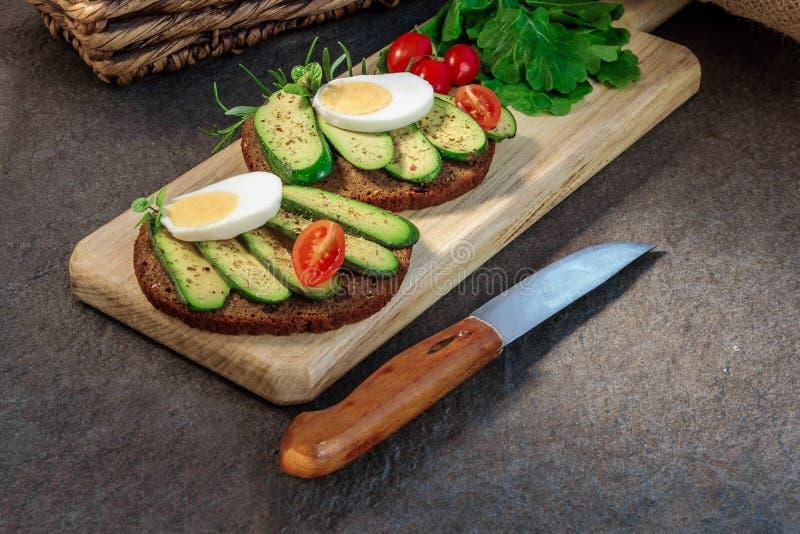 O sanduíche com o tomate sem sementes na placa de corte, faca do abacate, do ovo e de cereja está próximo Abacate sem alguma seme foto de stock royalty free