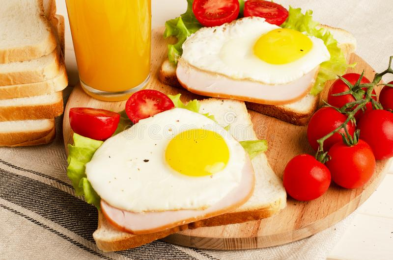 O sanduíche de presunto com ovo mexido, tomate, alface, deliciosa cura foto de stock royalty free