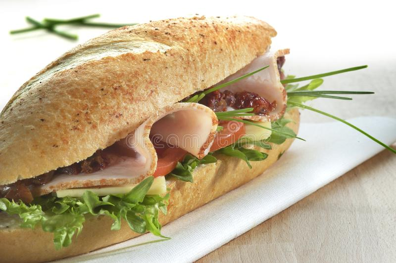 O sanduíche delicioso serviu em um guardanapo em uma tabela imagem de stock