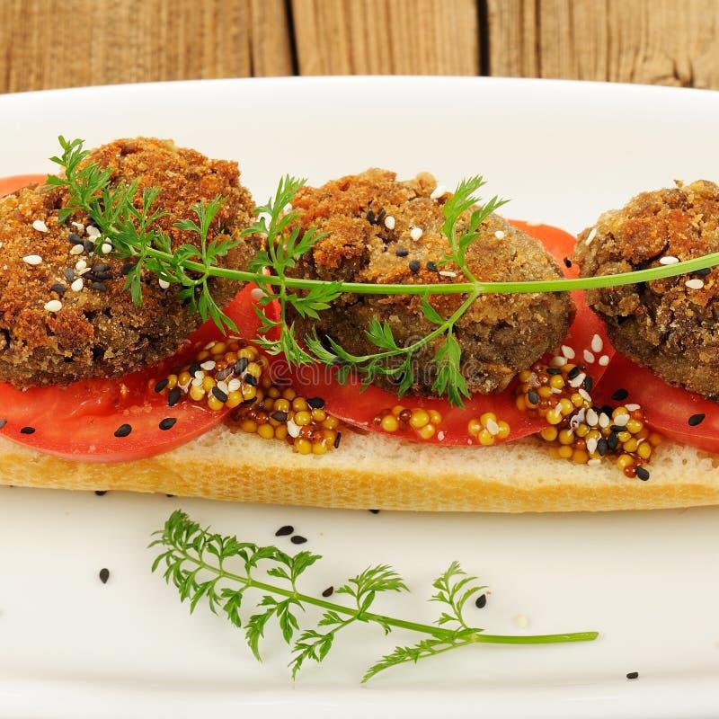 O sanduíche do rissol da lentilha com tomate, as sementes de sésamo e a cenoura esverdeiam imagens de stock