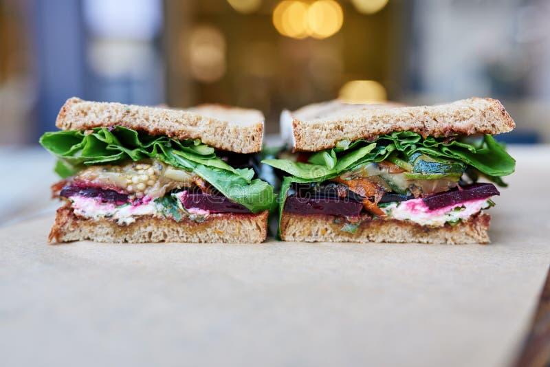 O sanduíche gourmet cortou ao meio que senta-se em uma tabela dos restaurantes imagens de stock royalty free