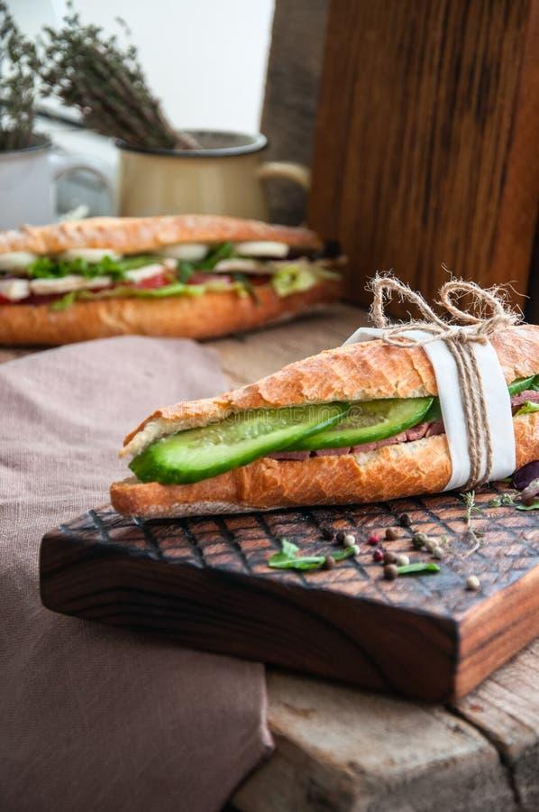 O sanduíche longo do baguette com bife corta o pepino e a especiaria imagem de stock