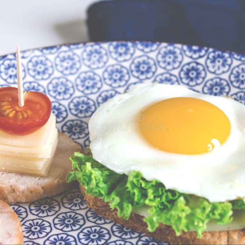 O sandu?che com ovo, presunto, queijo, brinde e salada deixa mentiras em uma placa com o tomate e o aneto fotos de stock