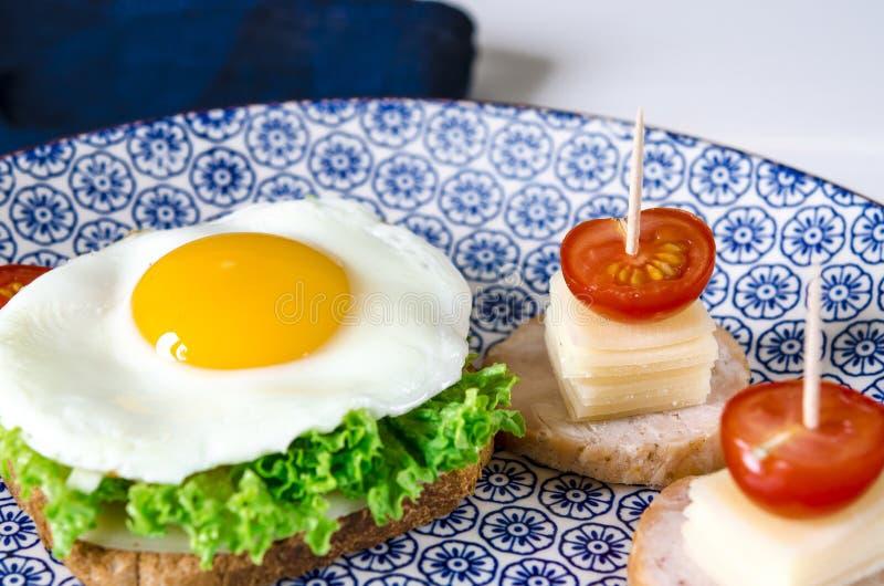 O sandu?che com ovo, presunto, queijo, brinde e salada deixa mentiras em uma placa com o tomate e o aneto imagem de stock