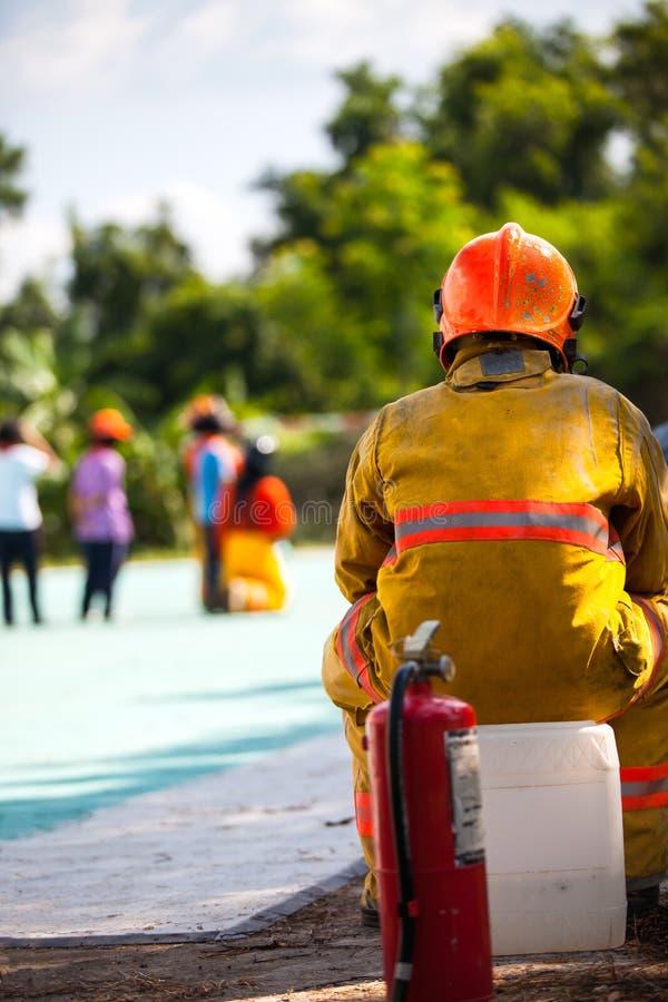 O sapador-bombeiro com fogo e o terno para protegem o bombeiro para sapadores-bombeiros de forma??o fotografia de stock royalty free