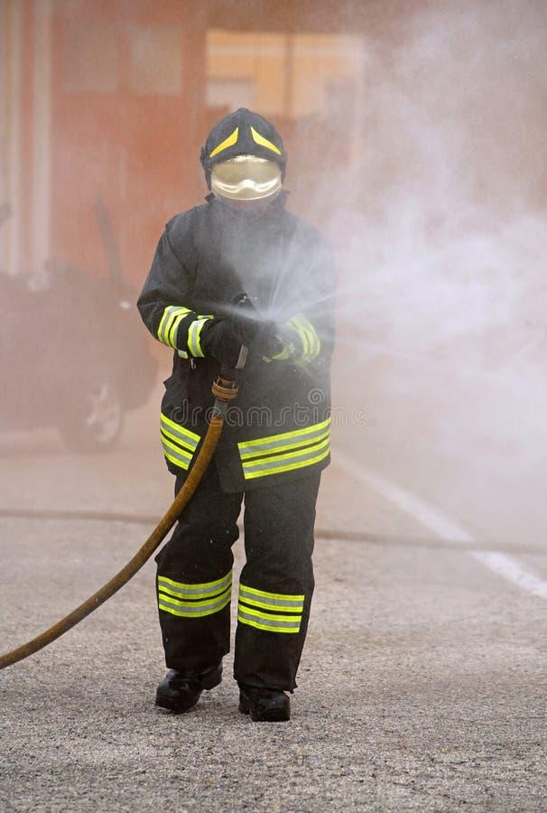 O sapador-bombeiro usa um agente de formação de espuma para extinguir um fogo fotos de stock