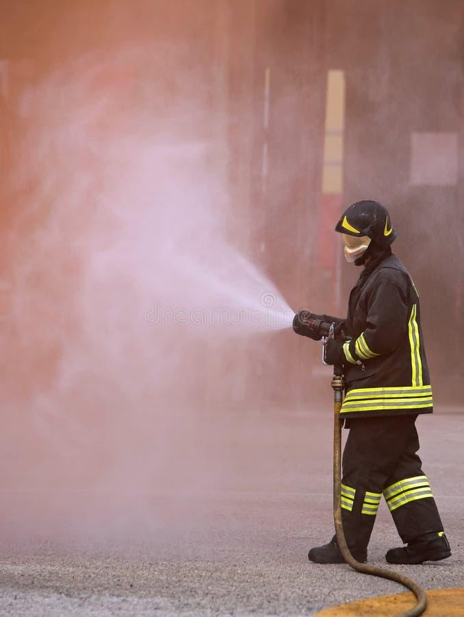 O sapador-bombeiro usa um extintor para extinguir um fogo imagens de stock