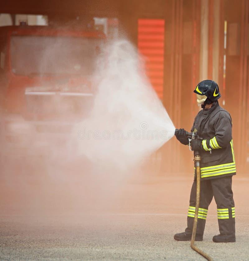 O sapador-bombeiro usa uma espuma para extinguir um fogo imagens de stock