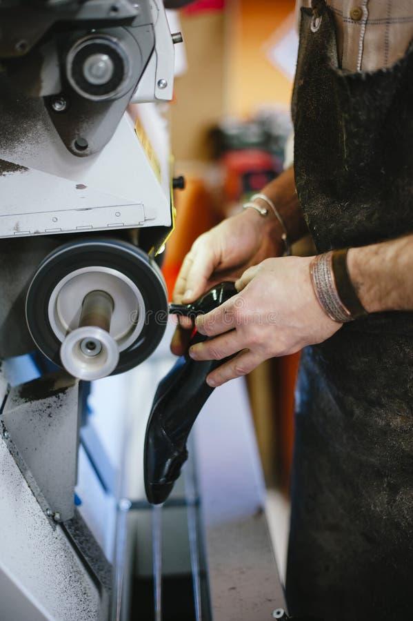 O sapateiro ajusta a sola da sapata em sua oficina imagem de stock royalty free