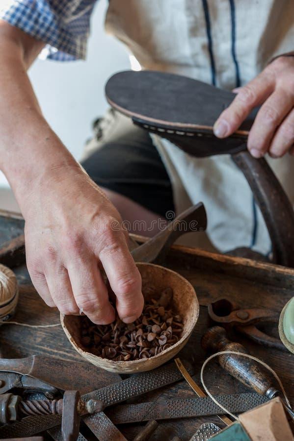 O sapateiro repara uma sapata em seu banco de trabalho imagem de stock