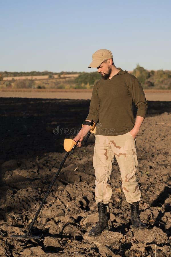 O sapper militar com um detector de metais examina o solo no campo para a presença de minas imagens de stock royalty free