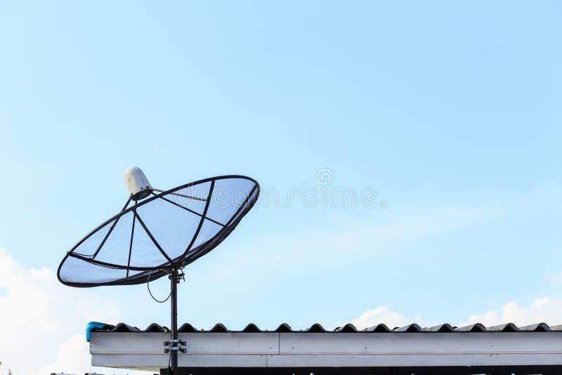 O satélite preto instala no telhado da casa com céu azul foto de stock