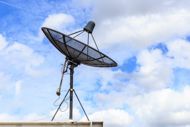 O satélite preto instala no telhado da casa com céu azul fotografia de stock royalty free