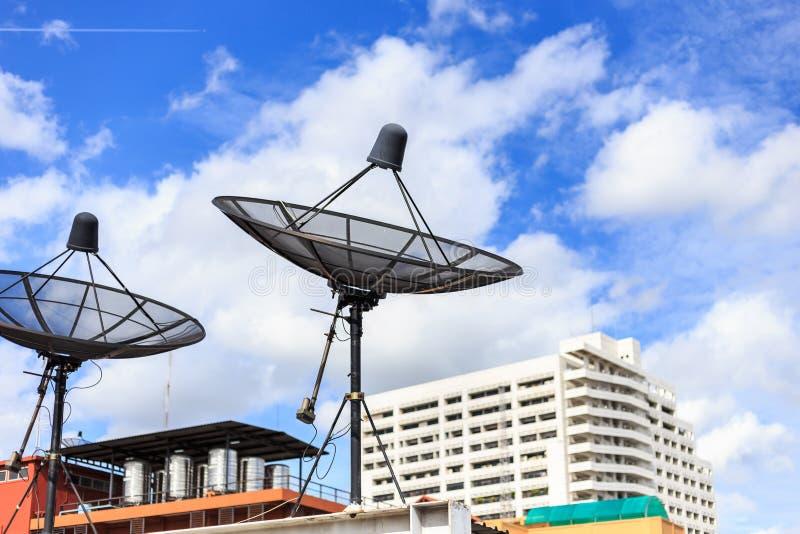 O satélite preto instala no telhado da casa com céu azul imagem de stock