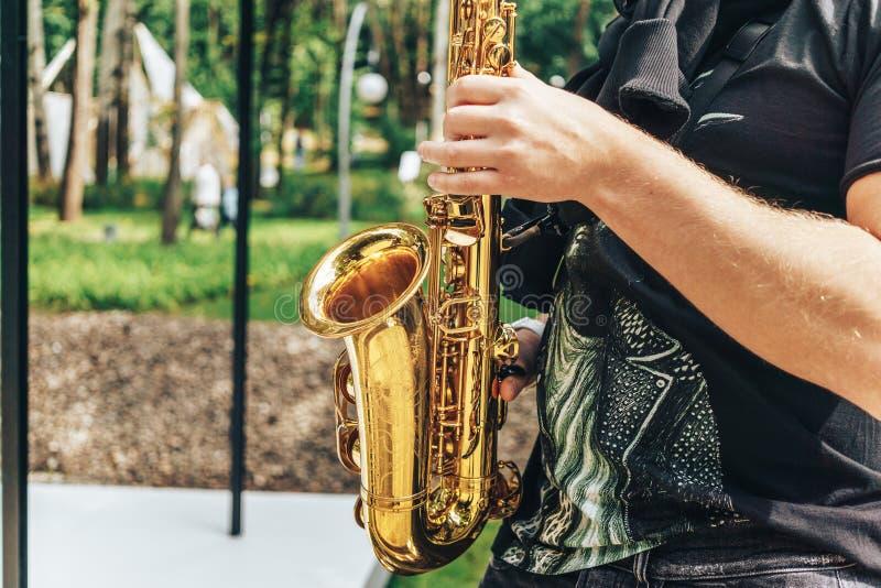O saxofonista do músico da rua joga a música jazz no parque no dia ensolarado imagens de stock