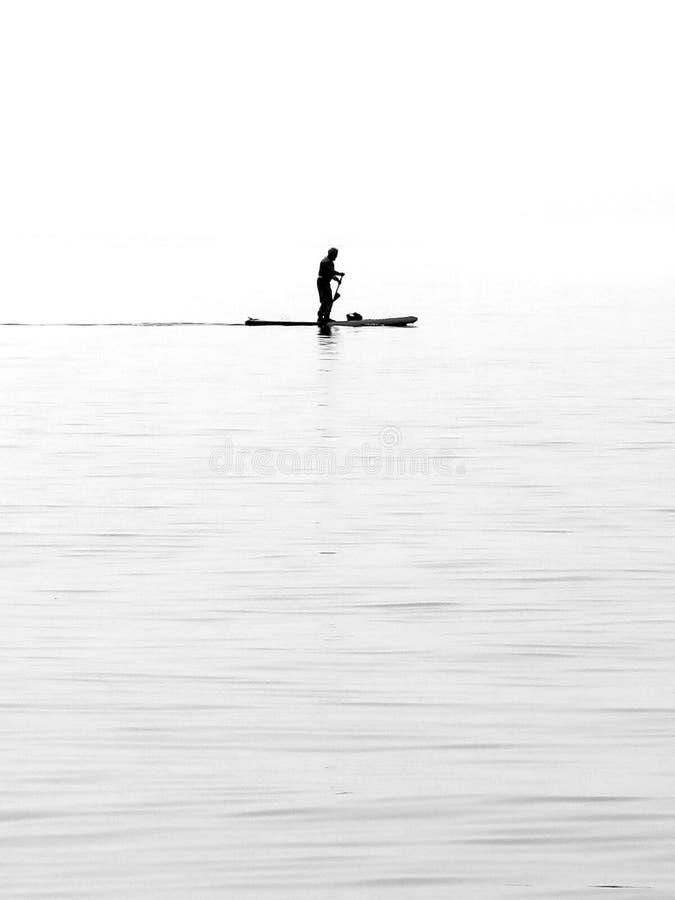 O Seascape e a paisagem natural veem o paddler só com água christal na praia do lago Garda Lazise, Itália foto de stock royalty free