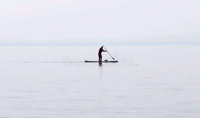 O Seascape e a paisagem natural veem o paddler só com água christal na praia do lago Garda Lazise, Itália fotos de stock royalty free
