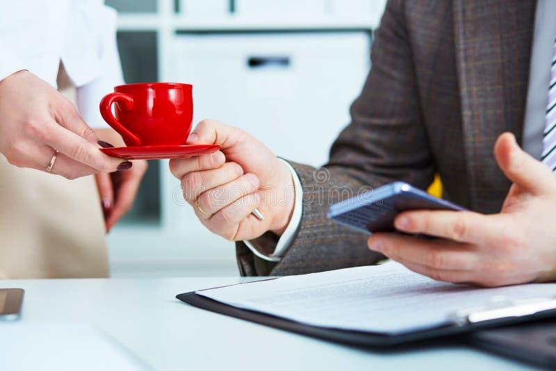 O secretário novo traz o café ao chefe masculino Pessoal de serviço Conceito do tempo do café e hora para uma ruptura foto de stock royalty free