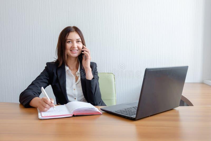 O secretário ocupado está respondendo à chamada e está escrevendo o memorando ao mesmo tempo fotografia de stock royalty free
