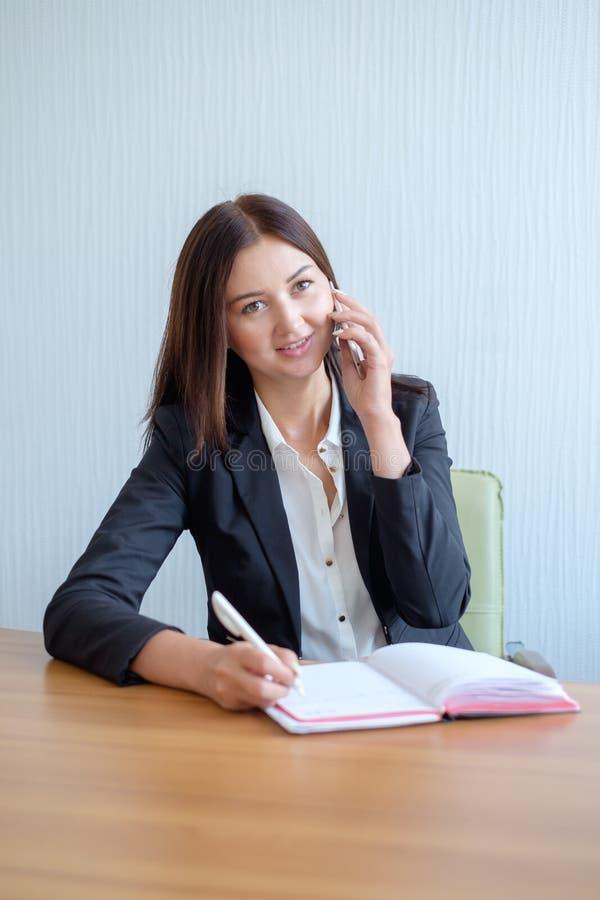 O secretário ocupado está respondendo à chamada e está escrevendo o memorando ao mesmo tempo imagens de stock royalty free