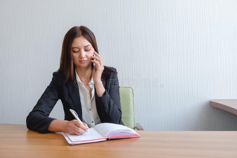 O secretário ocupado está respondendo à chamada e está escrevendo o memorando ao mesmo tempo imagem de stock royalty free