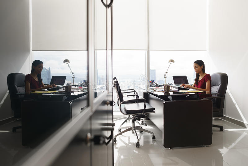O secretário redige a mensagem de correio eletrónico no PC da tabuleta na mesa de escritório fotografia de stock